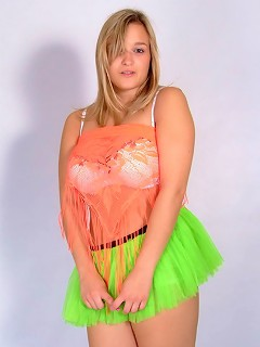 Big tit teen teases in a bright orange top and green tutu.