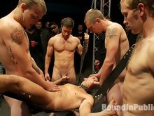 Studly Shane Frost gets tied up in the sling and fucked in front of 50 horny guests.