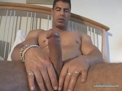 Strong and well hung stud jerking off on the bed