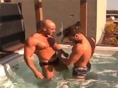 Big and muscled gay men having fun in the pool