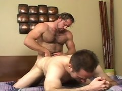 A muscled and hairy gay man barebacking his strong buddy's asshole on the bed