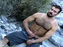 A big hairy bear masturbates his muscled hummer out of doors