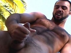 JD Kollin is cooling off in front of a huge water fountain playing with his fur covered pecs and nipples. The camera captures his hairy physique perfe