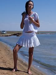 Sexy brunette teen posing bottomless on the beach